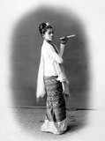 The cheroot that the young woman holds is a typical attribute in studio portraits of Burmese women, whose custom of smoking large cigars was noted with some astonishment by European visitors, who also commented on their relative freedom, beauty and confidence.<br/><br/>  She wears a striped silk <i>hta-mein</i> (wrap-around skirt) and a close-fitting jacket of fine muslin or cotton known as an <i>ein-gyi</i>. Her hair is adorned with a floral headband and she wears necklaces and earrings.<br/><br/>  During the Konbaung Dynasty (1752-1885), rich jewellery, fine fabrics such as silk and garments such as her jacket were reserved for court officials and their wives by law. After the fall of the Burmese monarchy in 1885 they were worn by the wealthy.<br/><br/>  This photograph is from an album recording aspects of Lord Elgin's Burma tour of November to December 1898. Victor Alexander Bruce (1849-1917), 9th Earl of Elgin and 13th Earl of Kincardine, served as Viceroy of India between 1894 and 1899.
